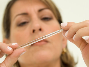 a woman using a thermometer